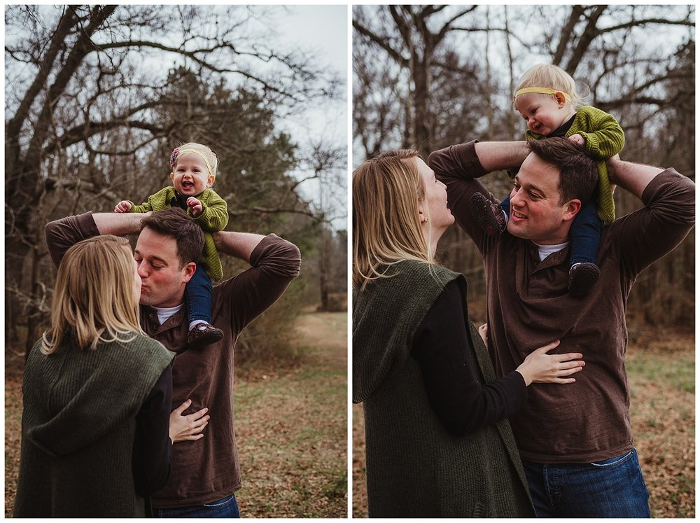 The baby giggles on daddy's shoulders as mom and dad have a kiss during their family photo shoot in Wake Forest, North Carolina.