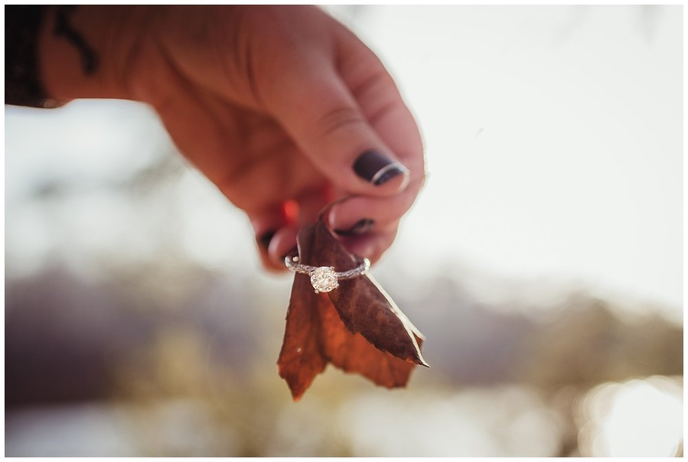 Her engagement ring, a beautiful diamond with a band that looks like tree bark, gets a close up during their engagement shoot at Durant Nature Park in Raleigh.