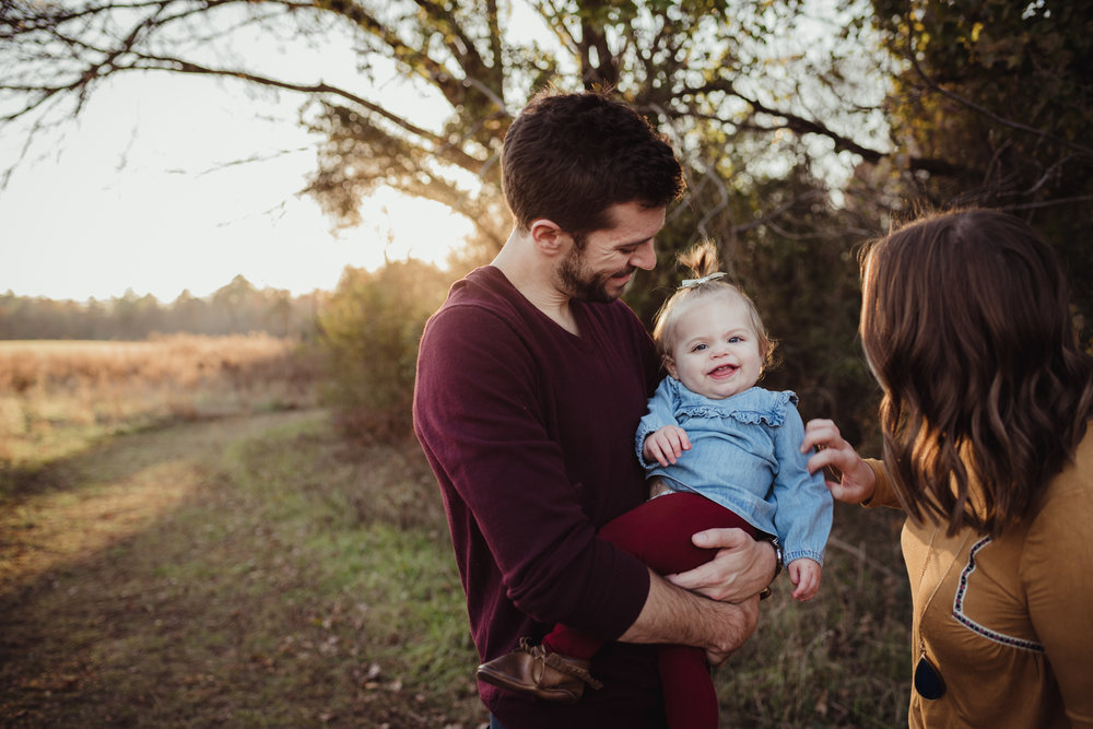 This young family of three tickles their young daughter at sunset during their family session with Rose Trail Images in Wake Forest, NC.
