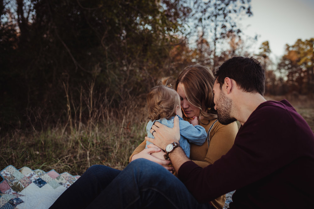 The family takes a moment to console their young daughter at sunset during their family photo session with Rose Trail Images at Horseshoe Nature Park in Wake Forest, NC.