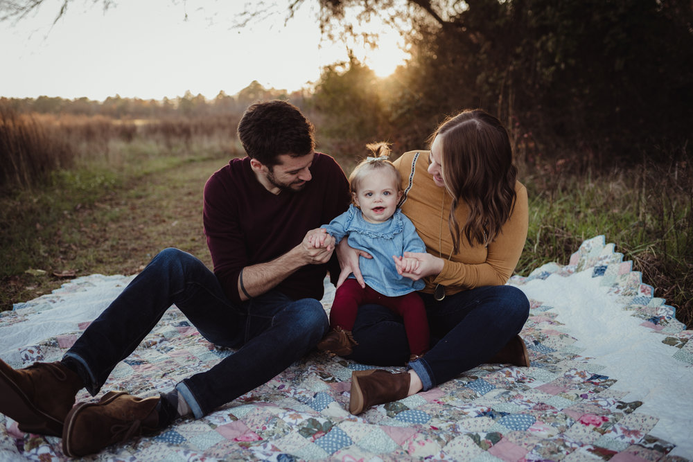 This young family of three sits on an old quilt with their young daughter at sunset during their family photo session with Rose Trail Images at Horseshoe Nature Park in Wake Forest, NC.