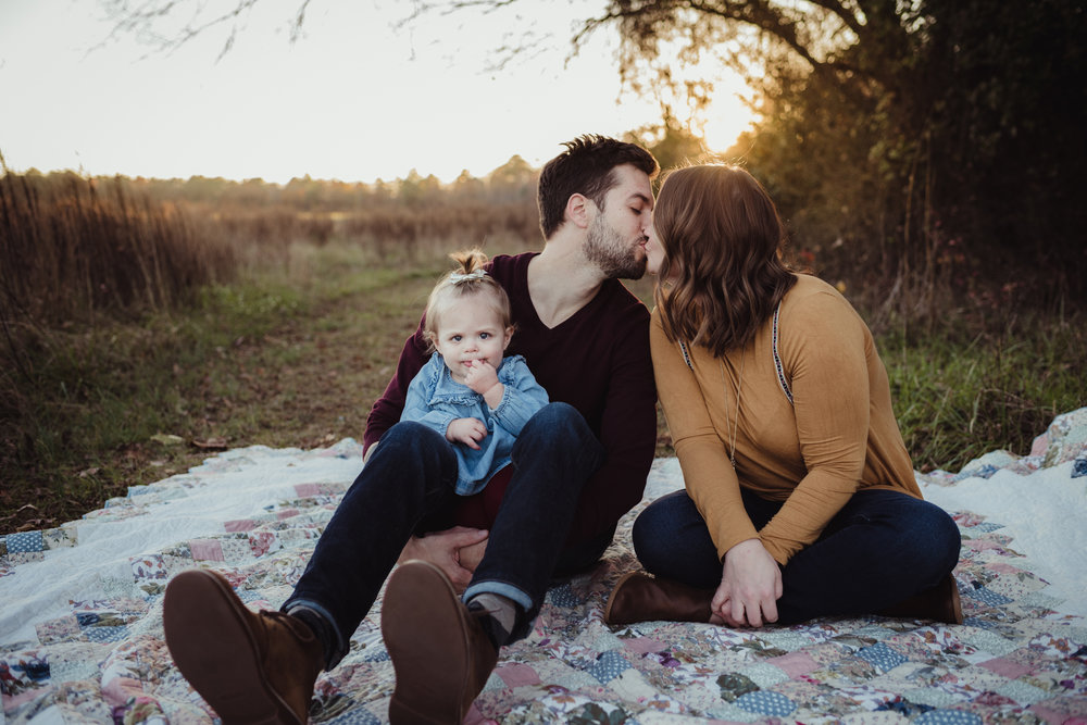 Mom and Dad kiss while their young daughter frowns at sunset during their family photo session with Rose Trail Images at Horseshoe Nature Park in Wake Forest, NC.