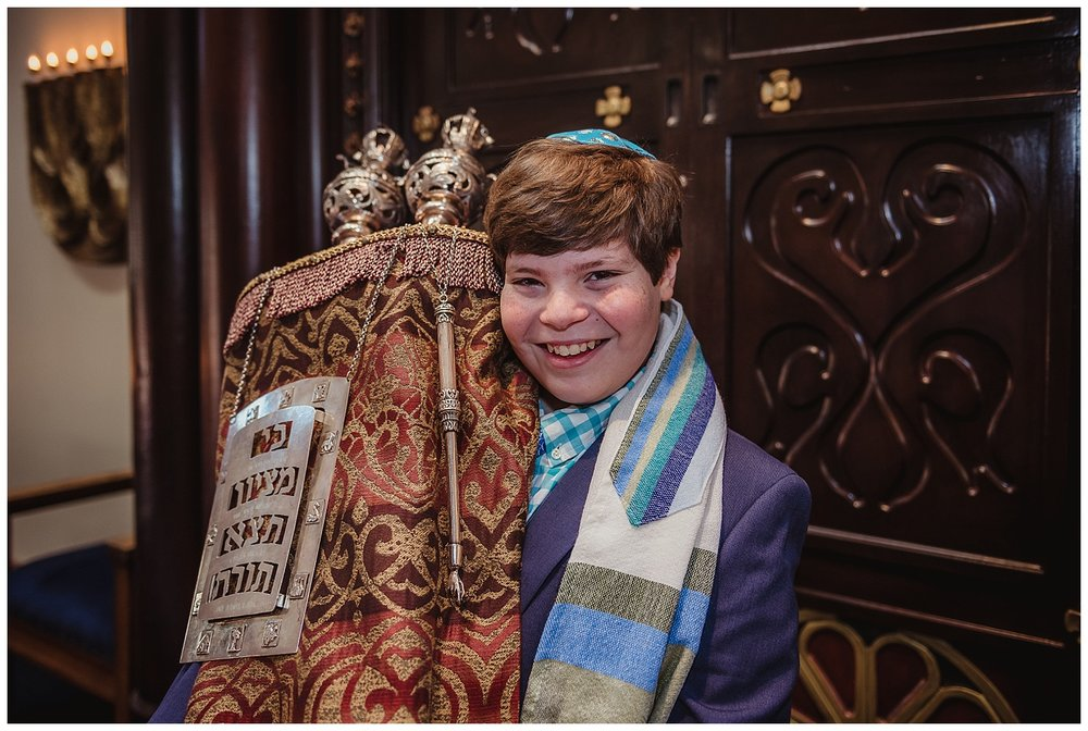 The bar mitzvah boy poses on the bema in front of the ark while holding the Torah at Temple Beth Or in Raleigh, NC.