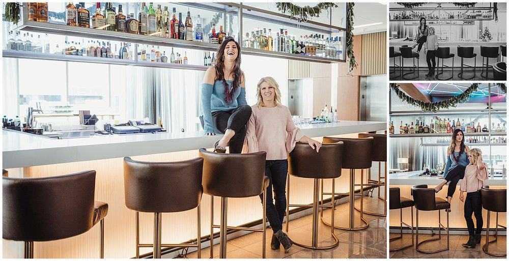 Sarah and Liz from Metro's Other Woman have a good laugh while posing for branding photos on the bar with Rose Trail Images at Level7 Rooftop Bar in Raleigh, NC.