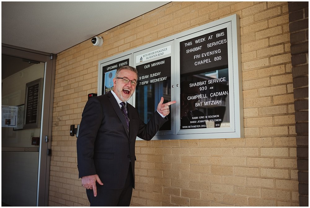 The father of the mitzvah girl poses withe sign out front at Beth Meyer Synagogue in Raleigh, NC.