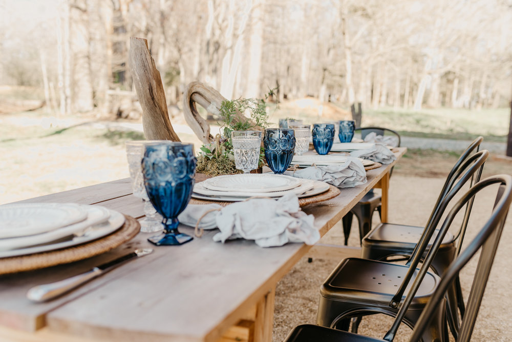 Succulents, blue glass ware, and driftwood adorn the table at the styled engagement session with Rose Trail Images at Windy Hill Farm near Raleigh, NC.
