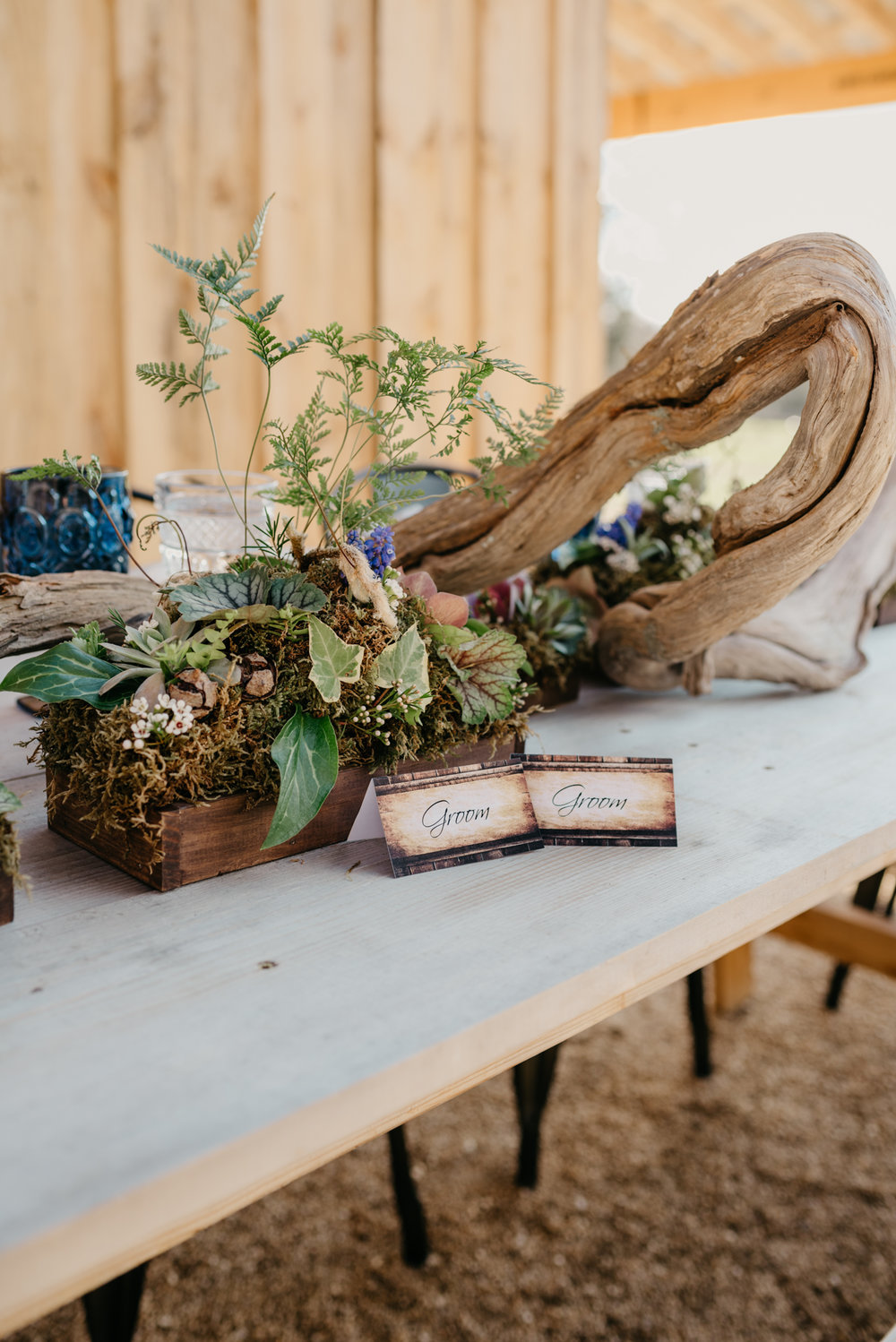 Groom and groom place cards, along with driftwood and glass wares, adorn the farm table at the styled engagement session with Rose Trail Images at Windy Hill Farm near Raleigh, NC.