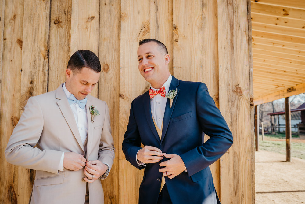 The grooms button up their vests and suits at their styled engagement session with Rose Trail Images at Windy Hill Farm near Raleigh, NC.