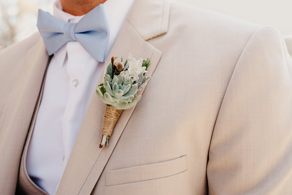 A close up of one of the grooms' cream colored boutonnieres at their styled engagement session with Rose Trail Images at Windy Hill Farm near Raleigh, NC.
