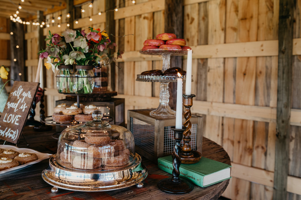 The rustic table decor at the reception is filled with candles, flowers, and different flavors of donuts, taken by Rose Trail Images at Windy Hill Farm near Raleigh, NC.