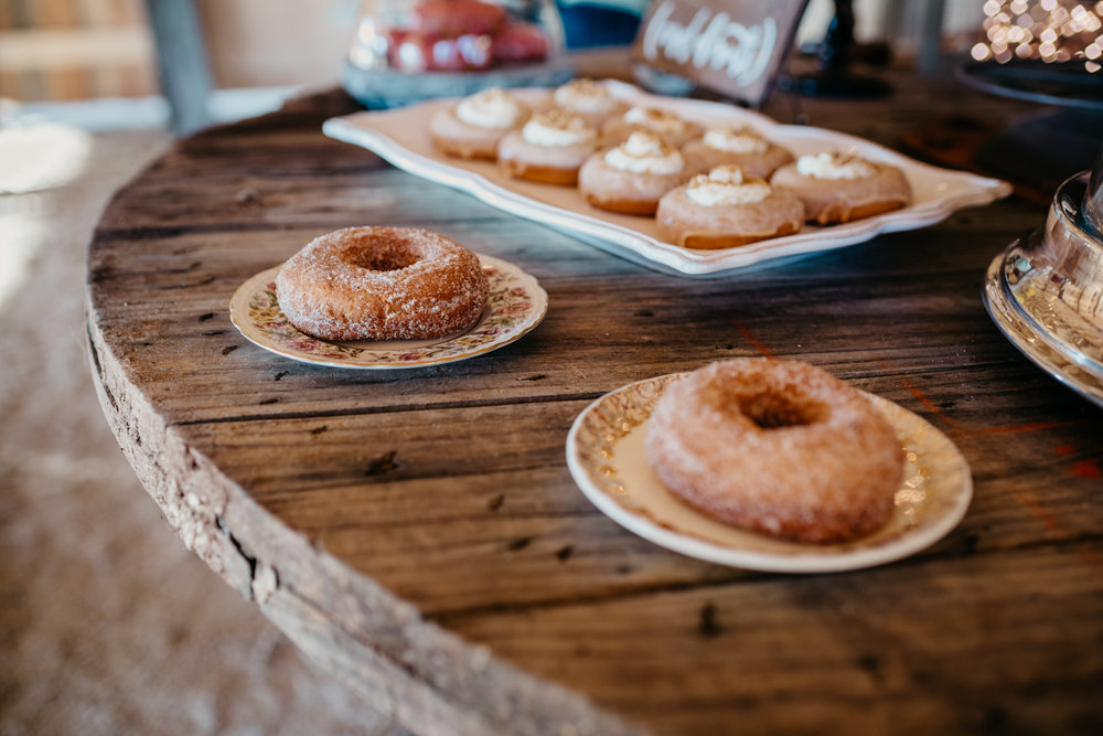 The rustic table decor at the reception is covered with different flavors of donuts, taken by Rose Trail Images at Windy Hill Farm near Raleigh, NC.
