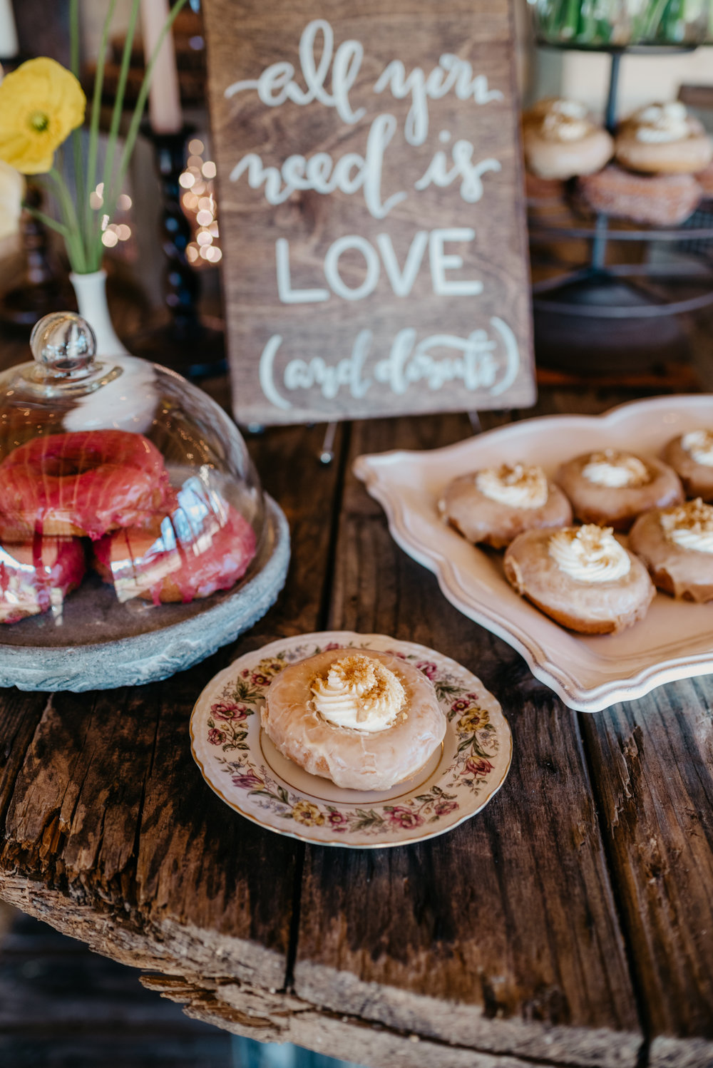 The rustic table decor at the reception is filled with flowers and different flavors of Monuts donuts, taken by Rose Trail Images at Windy Hill Farm near Raleigh, NC.