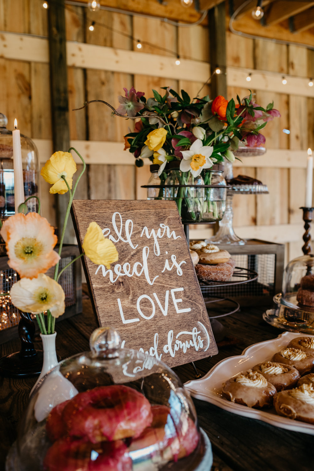 "The rustic table decor at the reception is filled with candles, flowers, and different flavors of donuts and a sign reading ""All you need is love and donuts"", taken by Rose Trail Images at Windy Hill Farm near Raleigh, NC."