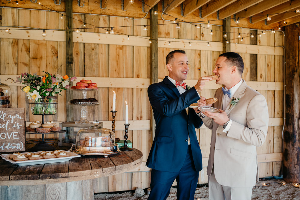 The rustic table decor at the reception is filled with candles, flowers, and different flavors of donuts, while the grooms feed donuts to each other, taken by Rose Trail Images at Windy Hill Farm near Raleigh, NC.