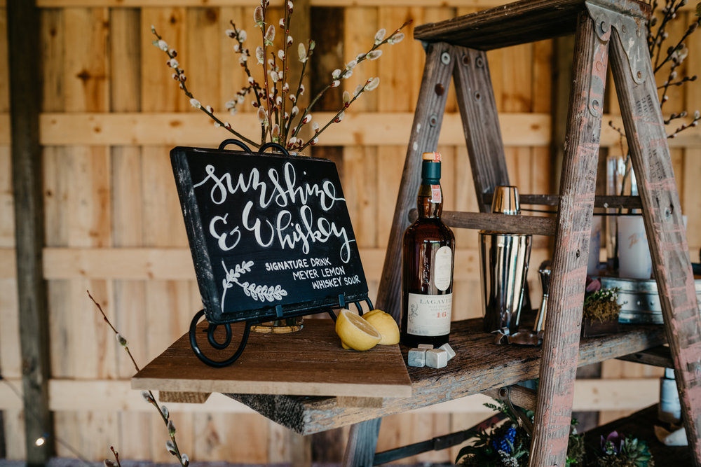 A rustic ladder is used as a whiskey station and is covered in whiskey, glasses, ice cubes, and ingredients to make a whiskey sour drink, taken by Rose Trail Images at Windy Hill Farm near Raleigh, NC.