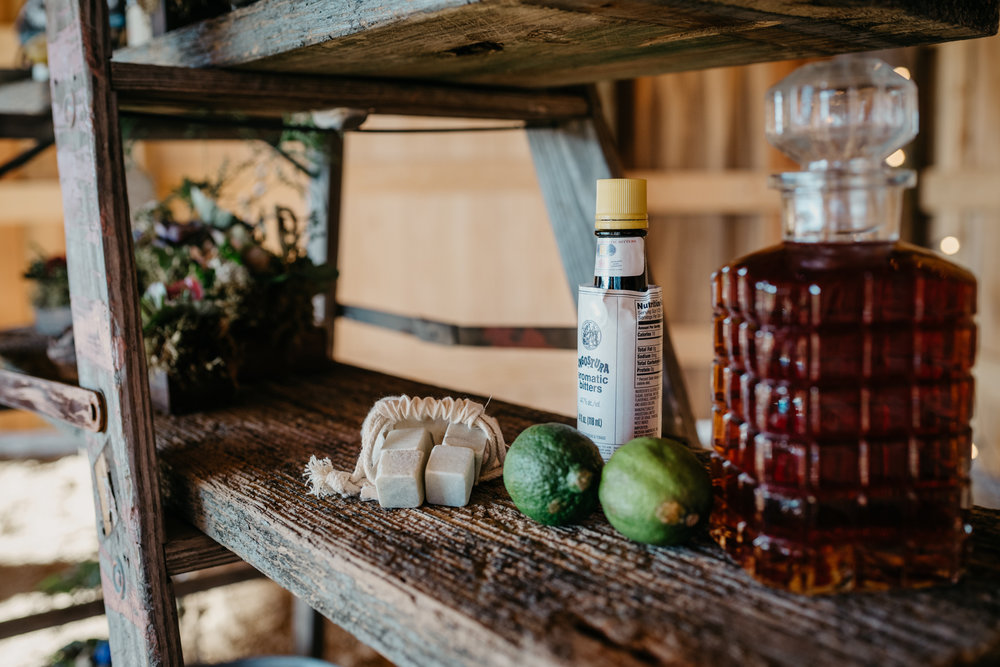 A rustic ladder is used as a whiskey station and is covered in whiskey, glasses, ice cubes, limes, and ingredients to make a whiskey sour drink, taken by Rose Trail Images at Windy Hill Farm near Raleigh, NC.