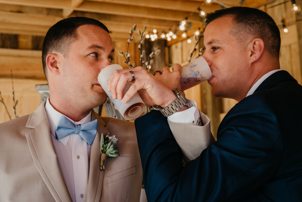 The grooms toast themselves with a whiskey sour drink during their styled engagement session with Rose Trail Images at Windy Hill Farm near Raleigh, NC.