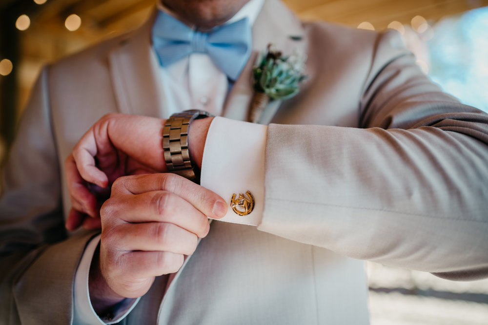 A close up of one of the grooms' horseshoe cufflinks at their styled engagement session with Rose Trail Images at Windy Hill Farm near Raleigh, NC.