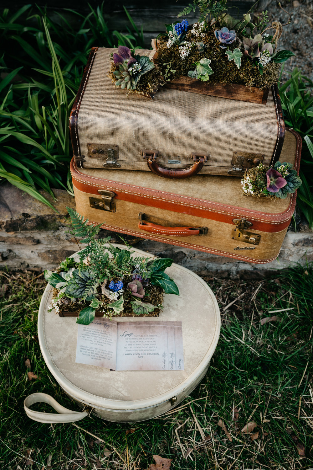 The suitcases, flowers, and invitations were setup outside by the barn at the rustic styled engagement session with Rose Trail Images at Windy Hill Farm near Raleigh, NC.