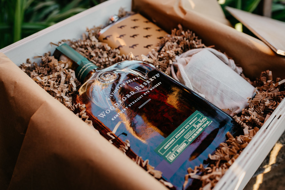 The grooms gave each other gift boxes with whiskey in them at the rustic styled engagement session with Rose Trail Images at Windy Hill Farm near Raleigh, NC.