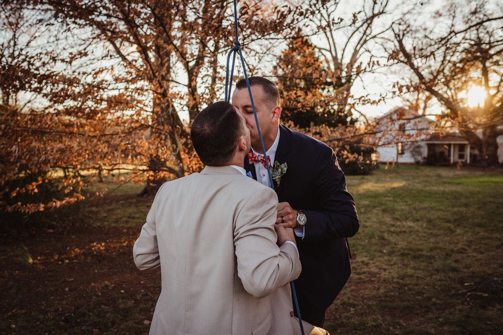 The grooms kissed on the swing outside by the barn at the rustic styled engagement session with Rose Trail Images at Windy Hill Farm near Raleigh, NC.