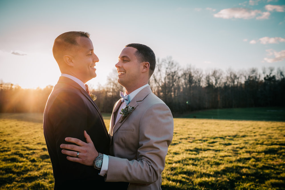 The grooms stand in the sunset at the rustic styled engagement session with Rose Trail Images at Windy Hill Farm near Raleigh, NC.
