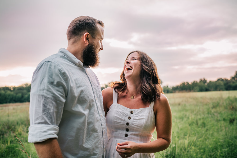 The couple laugh together during their engagement pictures with Rose Trail Images at Horseshoe Park in Wake Forest, North Carolina.
