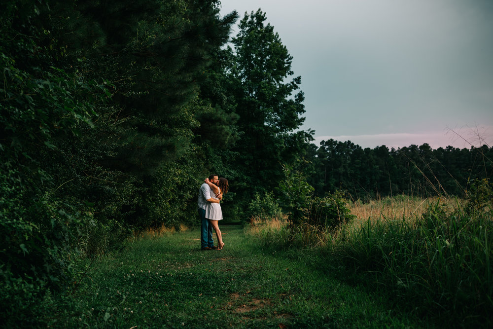 The couple share a kiss on the path at sunset for their engagement pictures with Rose Trail Images at Horseshoe Park in Wake Forest, North Carolina.