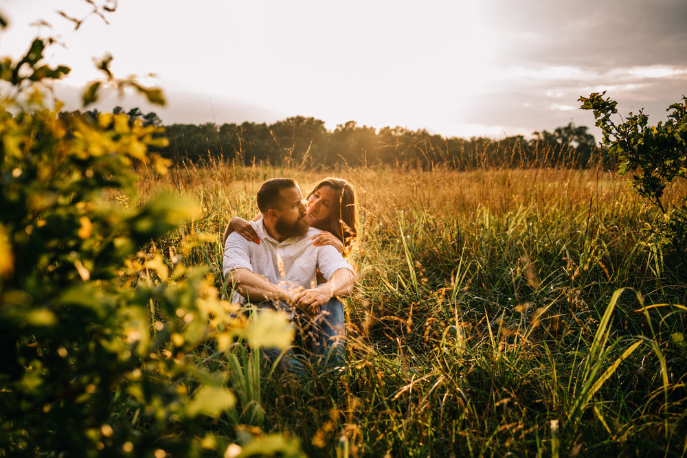 The couple sit in the summer field at sunset for their engagement pictures with Rose Trail Images at Horseshoe Park in Wake Forest, North Carolina.