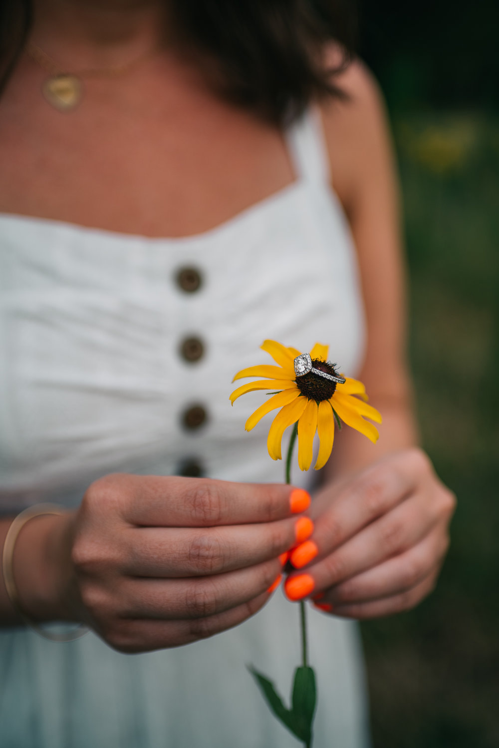 The bride, with her bright orange fingernails, shows off her engagement ring on a black-eyed susan flower during her engagement pictures with Rose Trail Images in Wake Forest, North Carolina.