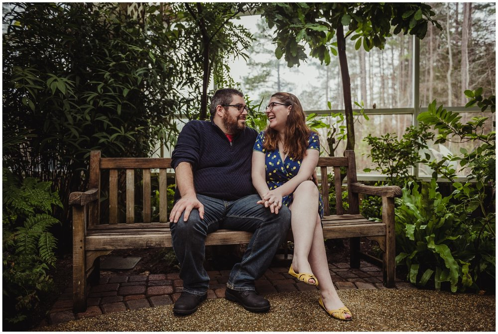 The bride-to-be and groom-to-be sit on a bench and laugh during their engagement photo session with Rose Trail Images at the Butterfly House in Durham.
