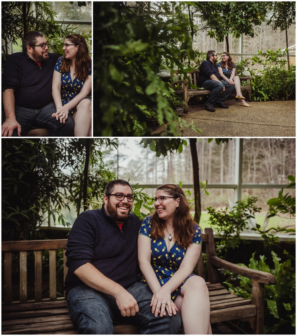 The couple sit on a bench and laugh during their engagement photo session with Rose Trail Images at the Butterfly House in Durham.