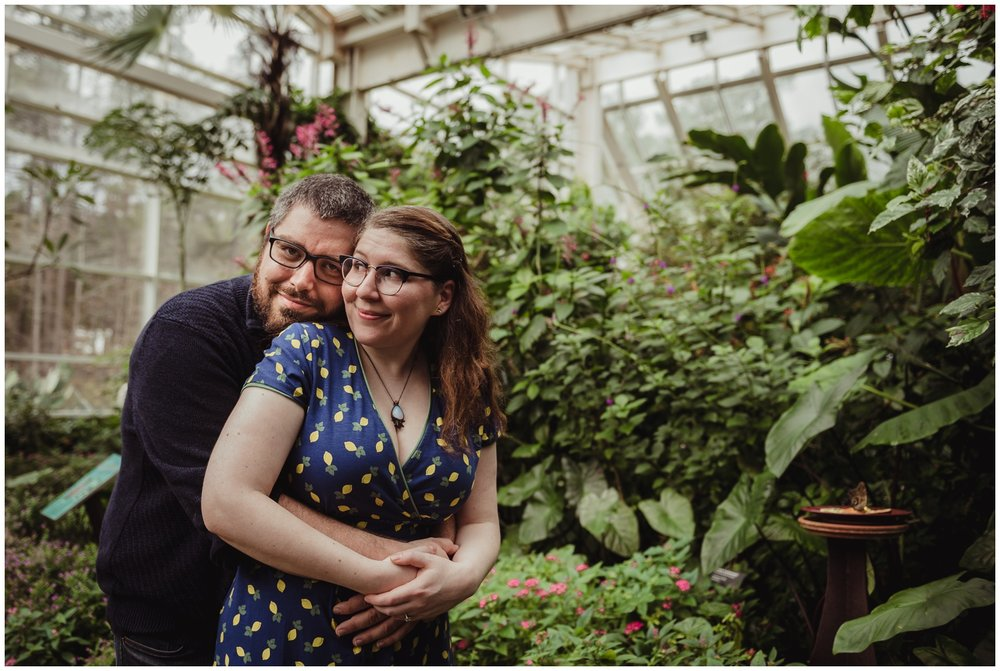 The future groom gives his future bride a hug in the Butterfly House during their engagement photo session with Rose Trail Images in Durham, NC.
