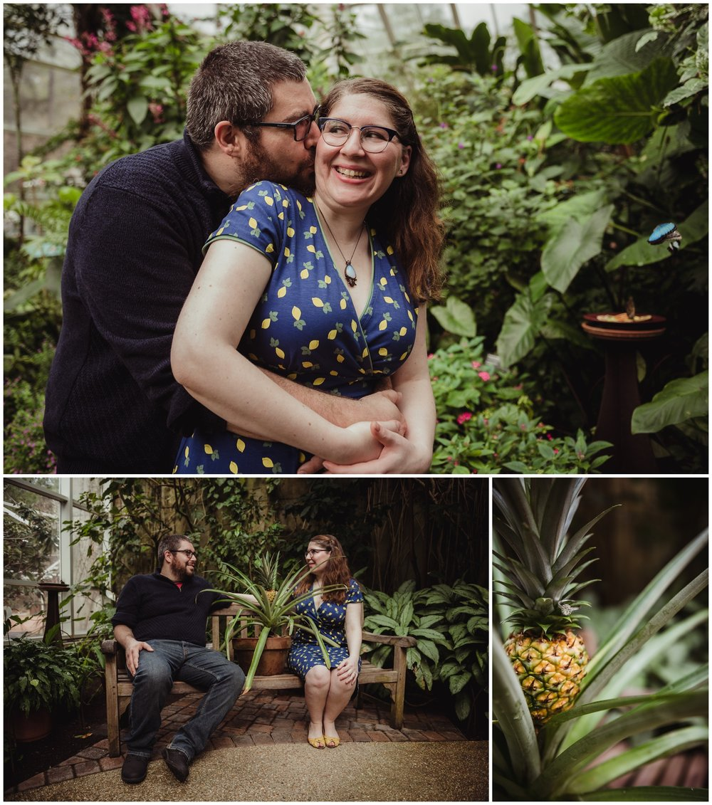 The couple take their pictures with a potted pineapple in the Butterfly House during their engagement photo session with Rose Trail Images in Durham, NC.