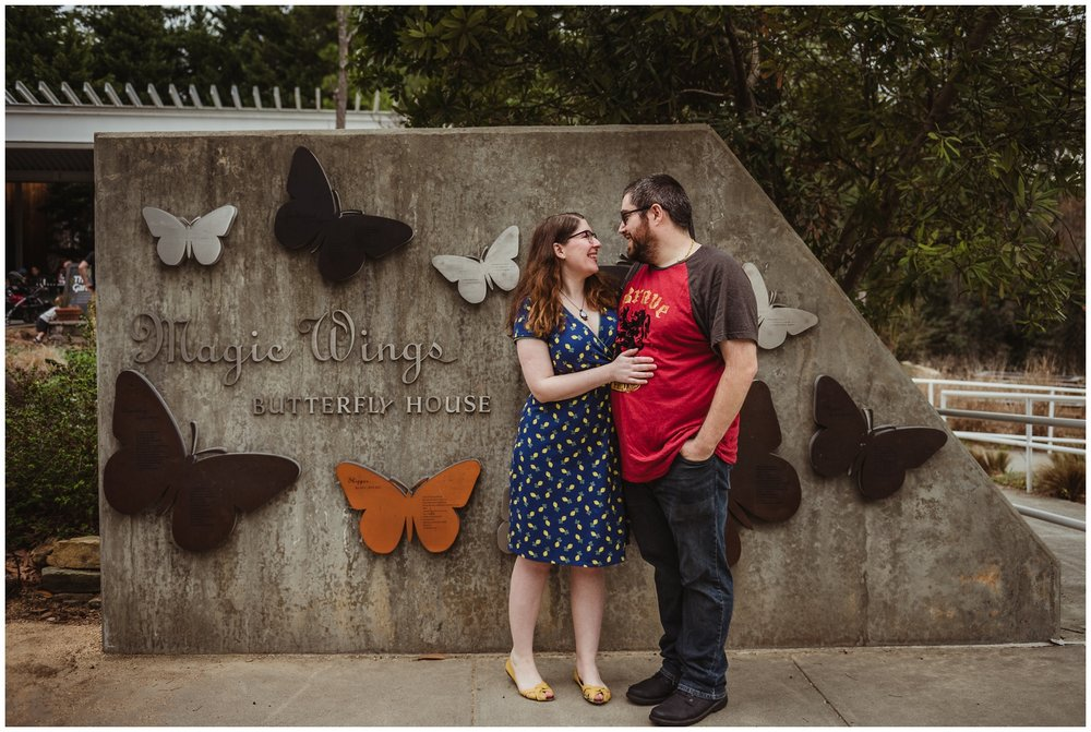 The couple stand outside the Butterfly House during their engagement photo session with Rose Trail Images in Durham, NC.
