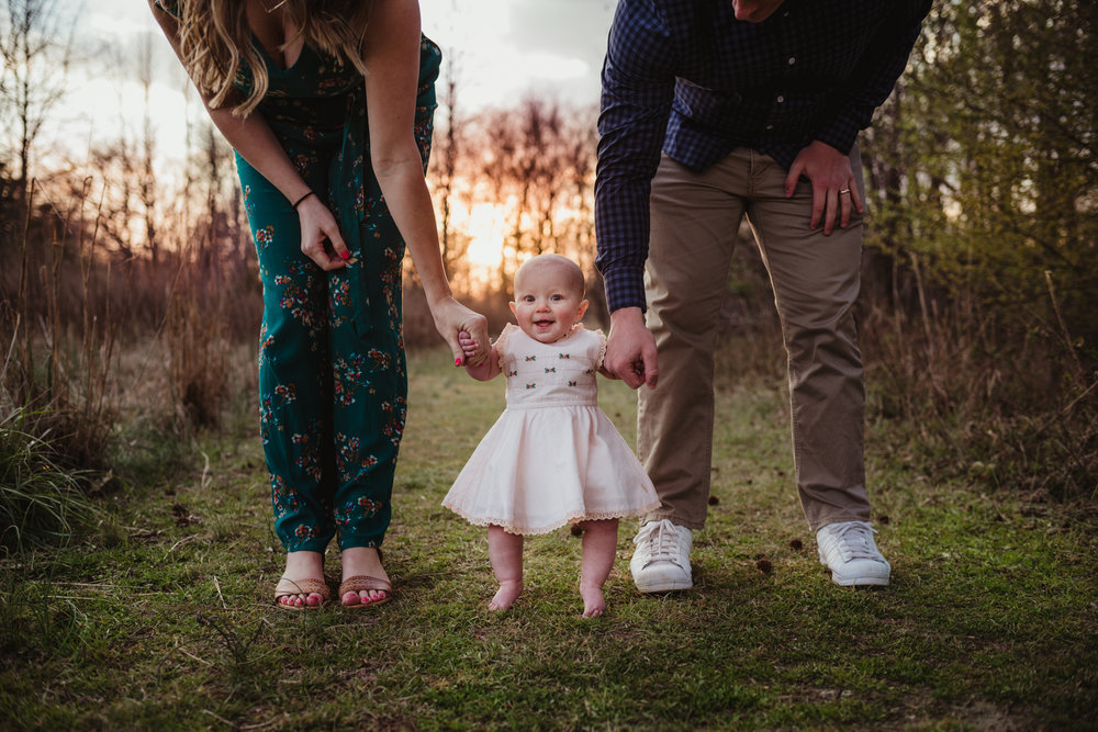 A couple walk with their 9-month old at sunset during their family photos with Rose Trail Images at Horseshoe Farm Park in Wake Forest, NC.