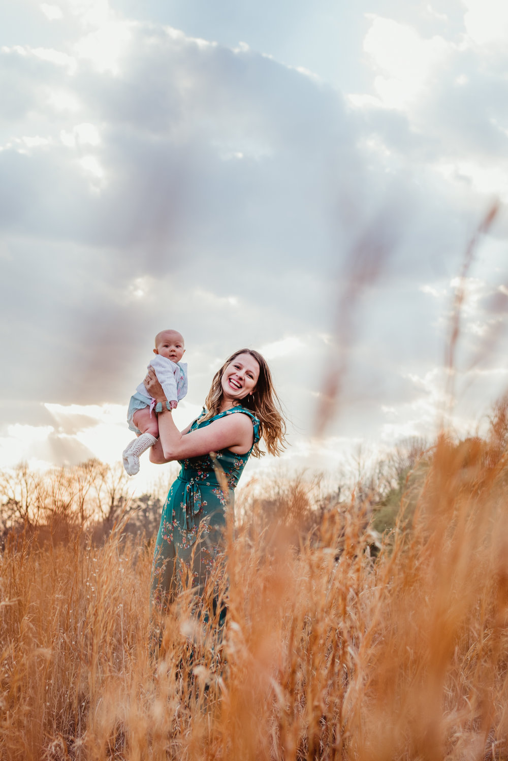 A mom plays with her 9-month old in the tall grass during their family photos with Rose Trail Images at Horseshoe Farm Park in Wake Forest, NC.