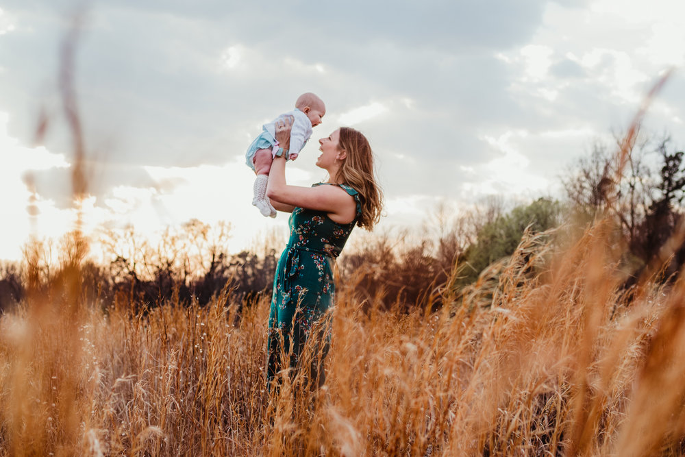 A mom plays with her 9-month old in the tall grass during their family photos at Horseshoe Farm Park in Wake Forest, NC with Rose Trail Images.