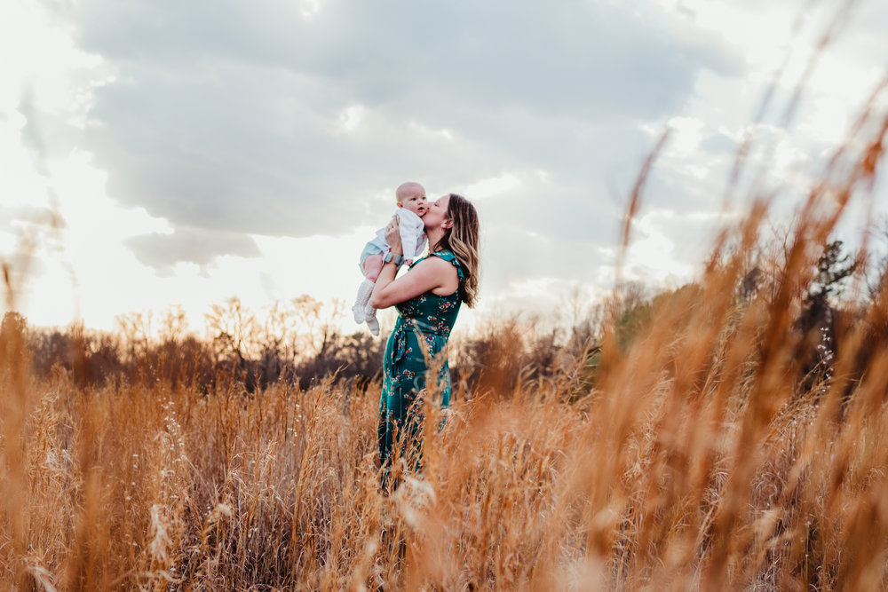 A mom kisses her 9-month old in the tall grass during their family photos with Rose Trail Images at Horseshoe Farm Park in Wake Forest, NC.
