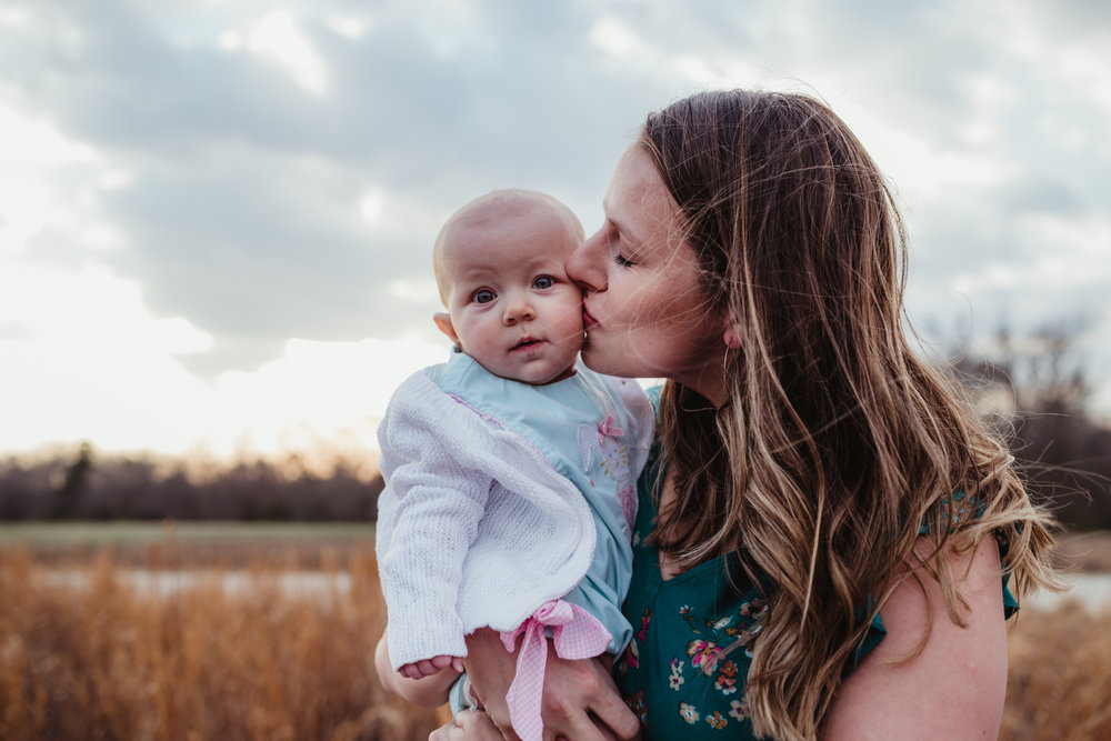A mom kisses her 9-month old during their family photos with Rose Trail Images at Horseshoe Farm Park in Wake Forest, NC.