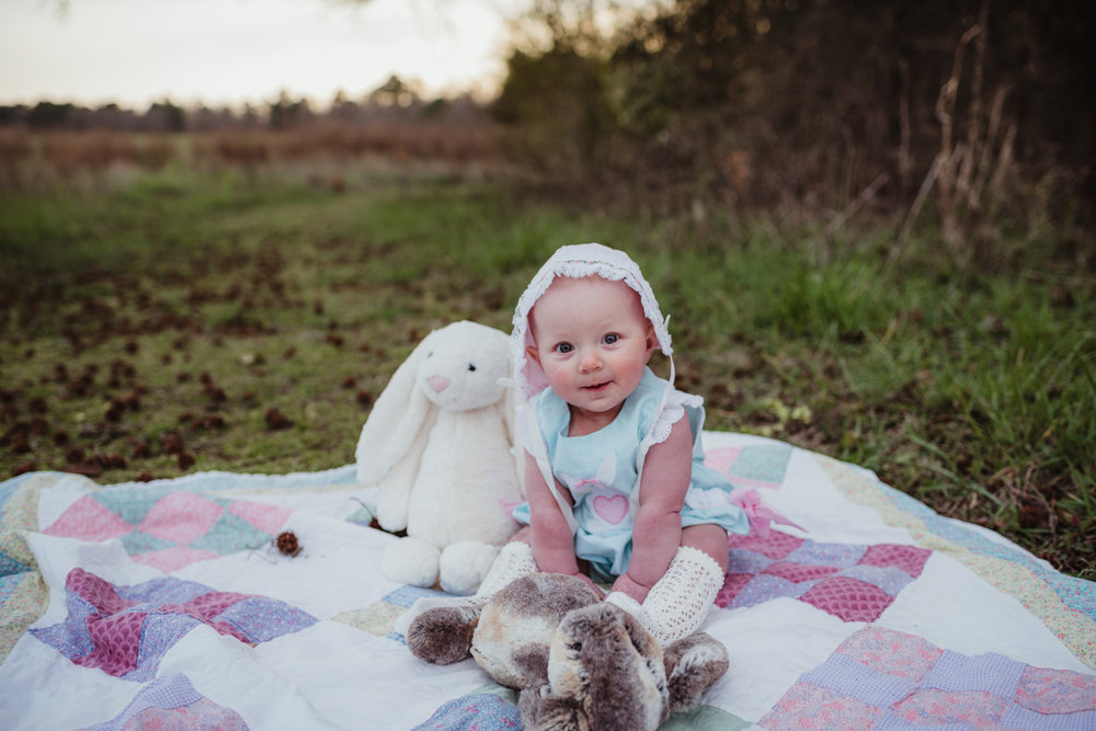 A 9-month old sits in her easter bonnet with her stuffed animals during their family photos with Rose Trail Images at Horseshoe Farm Park in Wake Forest, NC.