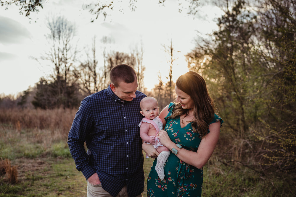 The family of three pose at sunset during their family photos with Rose Trail Images at Horseshoe Farm Park in Wake Forest, NC.
