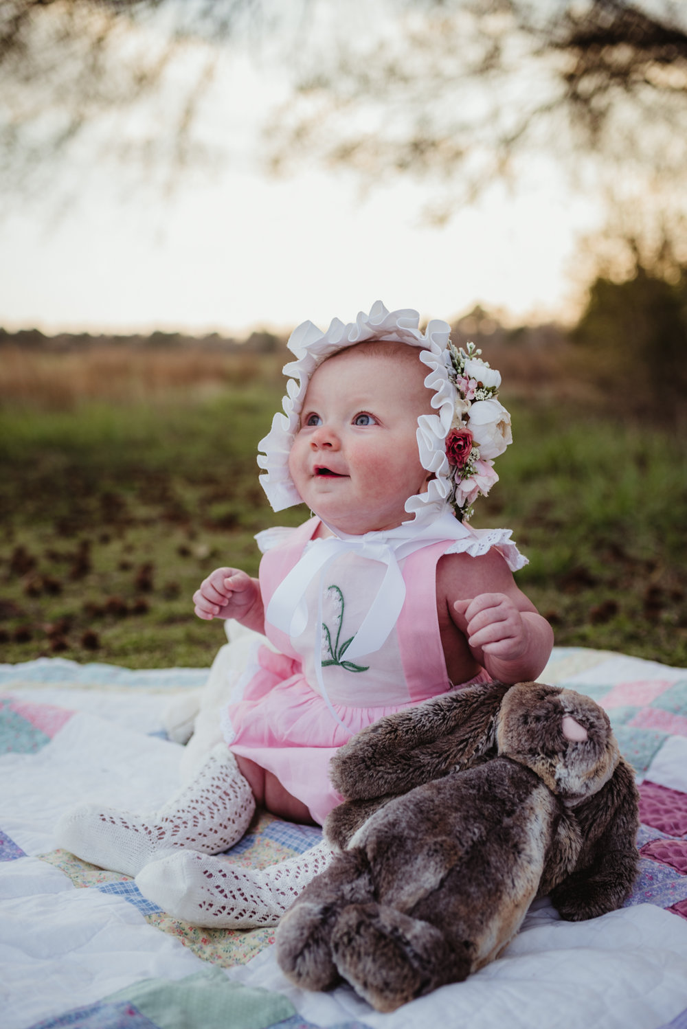 The baby poses on a family blanket with her Easter bonnet on at sunset during their family photos with Rose Trail Images at Horseshoe Farm Park in Wake Forest, NC.