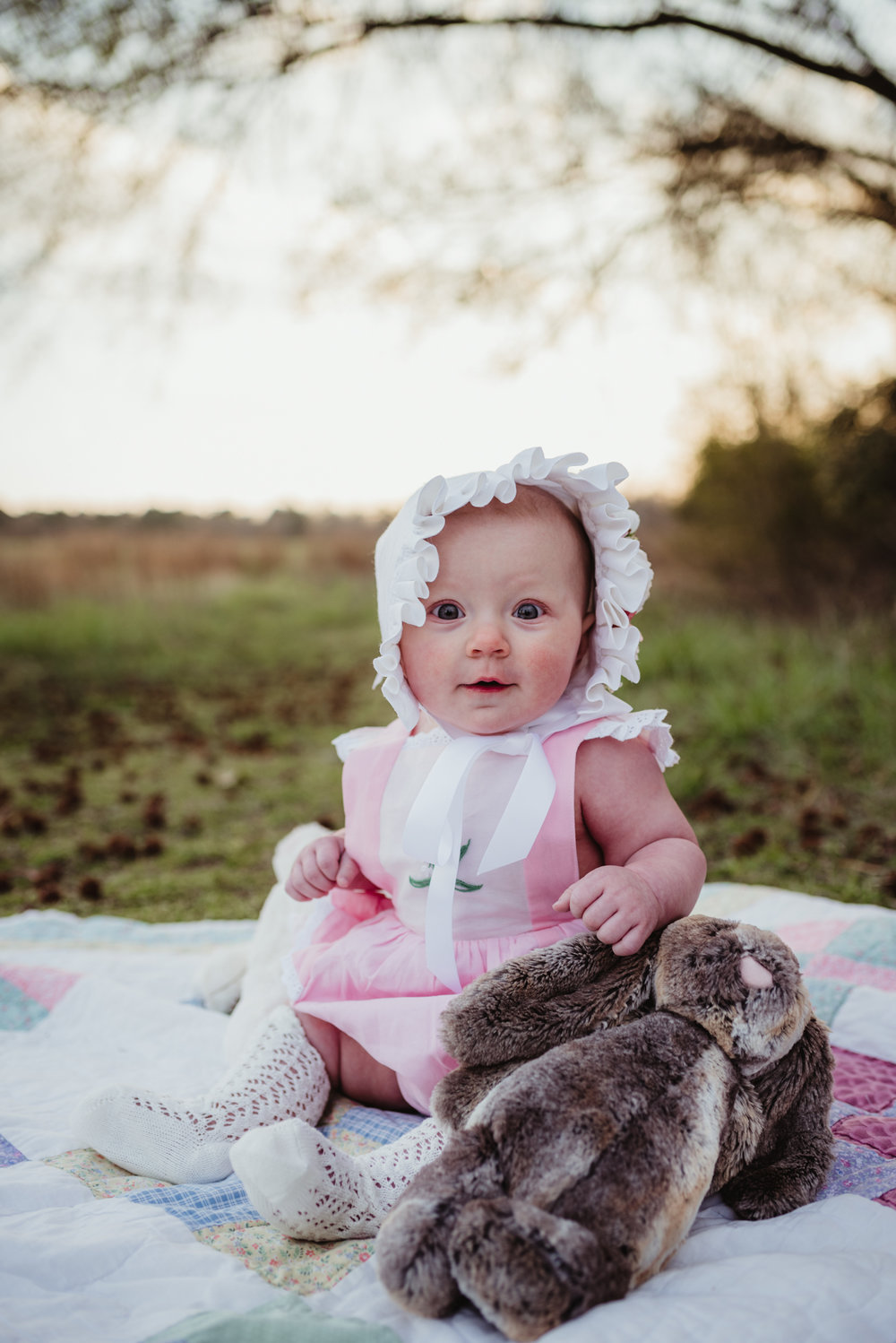 The baby poses on a family blanket with her Easter bonnet and stuffed animals at sunset during their family photos with Rose Trail Images at Horseshoe Farm Park in Wake Forest, NC.