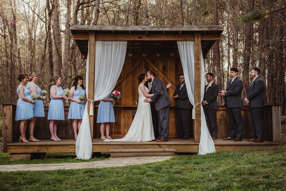 The bride and groom share a first kiss after their wedding ceremony at Carlee Farms in Oxford, NC, image taken by Rose Trail Images.