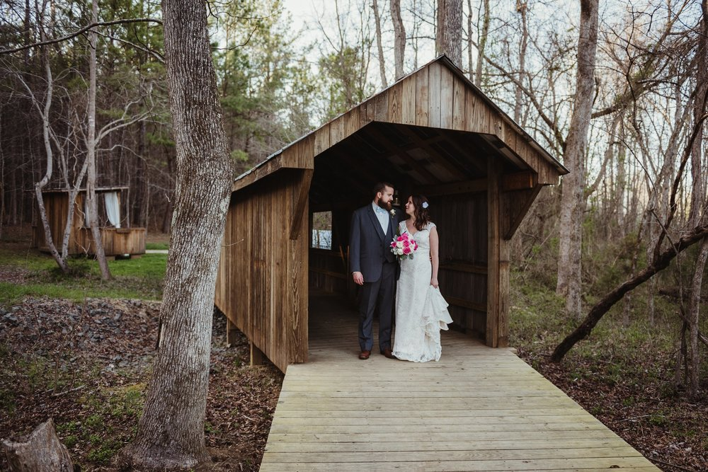 The bride and groom take pictures at the covered bridge after the wedding ceremony with Rose Trail Images at Carlee Farms in Oxford, NC.