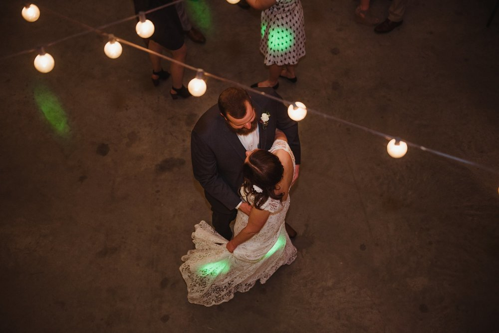 The bride and groom dance together under the market lights at Carlee Farm in Oxford, NC, taken by Rose Trail Images.