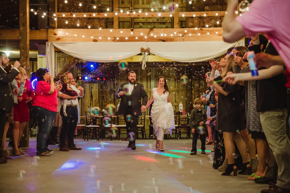 The bride and groom had a bubble exit at their wedding reception at Carlee Farm in Oxford, NC, taken by Rose Trail Images.