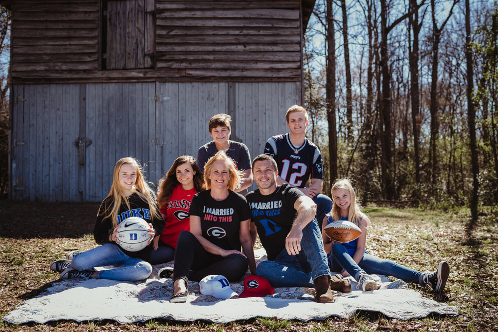 The couple sit together with their family, along with their Georgia Bulldogs and Duke BlueDevils attire during their engagement session with Rose Trail Images at a barn in Wake Forest, NC.