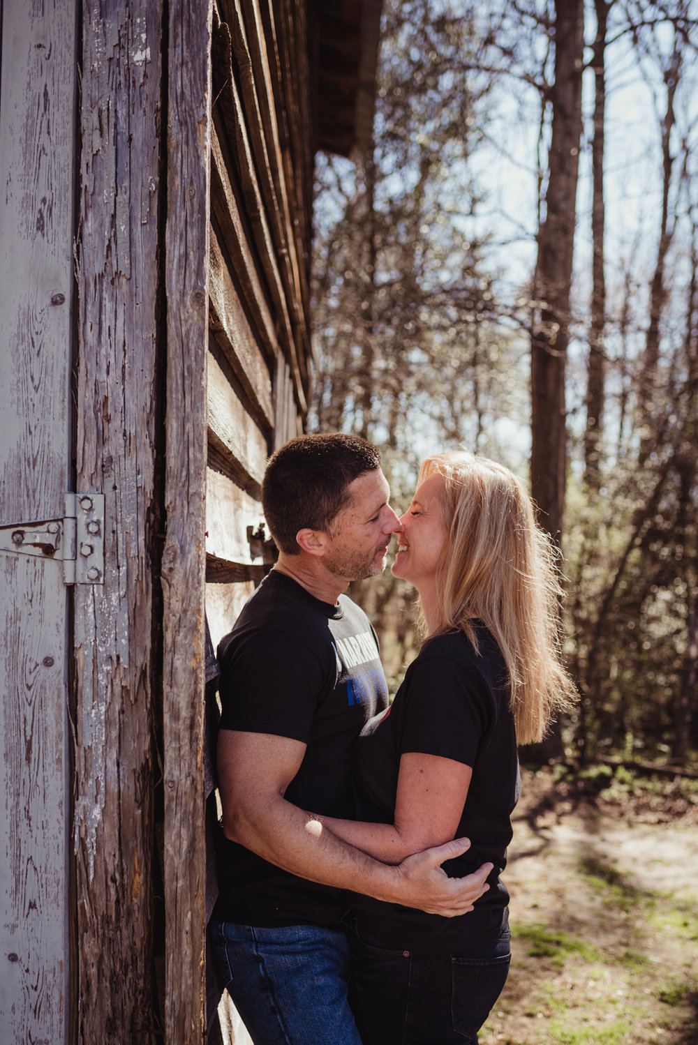 The couple hold each other on a barn in the morning light during their engagement session with Rose Trail Images in Wake Forest, NC.